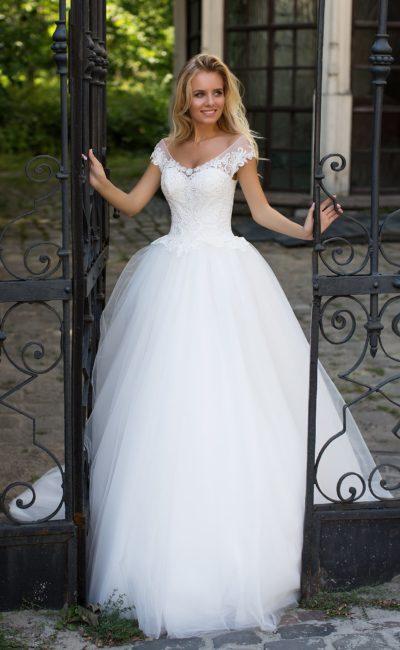 Пышное свадебное платье с кружевной отделкой и женственным округлым декольте.