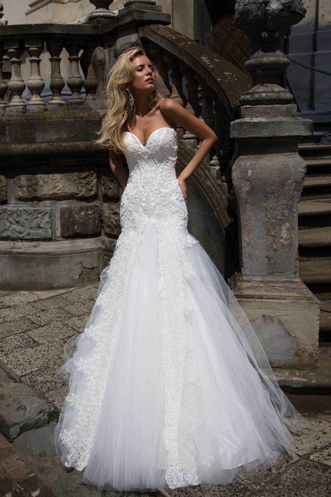 Открытое свадебное платье «рыбка» с кружевным декором корсета и многослойным подолом.