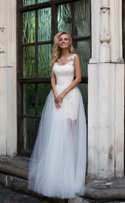 Романтичное свадебное платье с полупрозрачной верхней юбкой и кружевным декором верха.