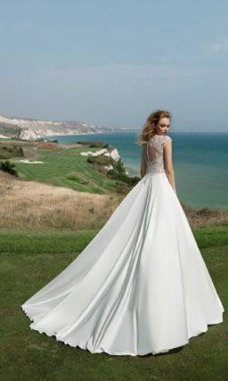 Стильное свадебное платье прямого кроя с атласной юбкой и кружевным верхом с коротким рукавом.