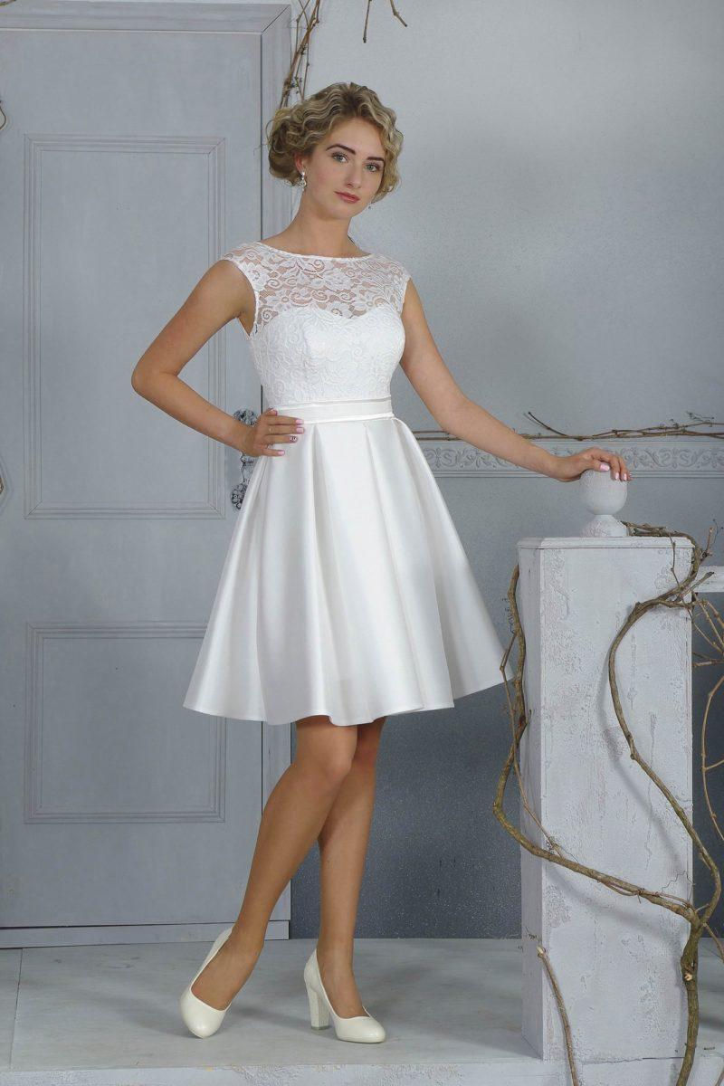 Короткое свадебное платье с атласной юбкой чуть выше колена и закрытым кружевным верхом.