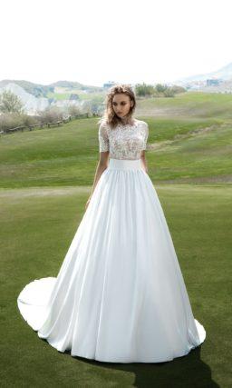 Роскошное свадебное платье пышного кроя с широким поясом и фигурным округлым вырезом.
