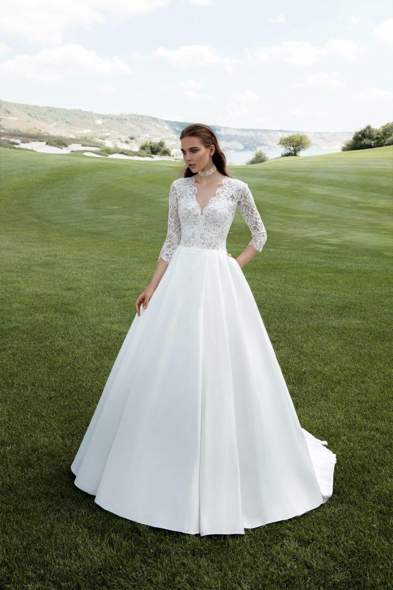 Свадебное платье с пышной атласной юбкой и кружевным лифом с V-образным вырезом.