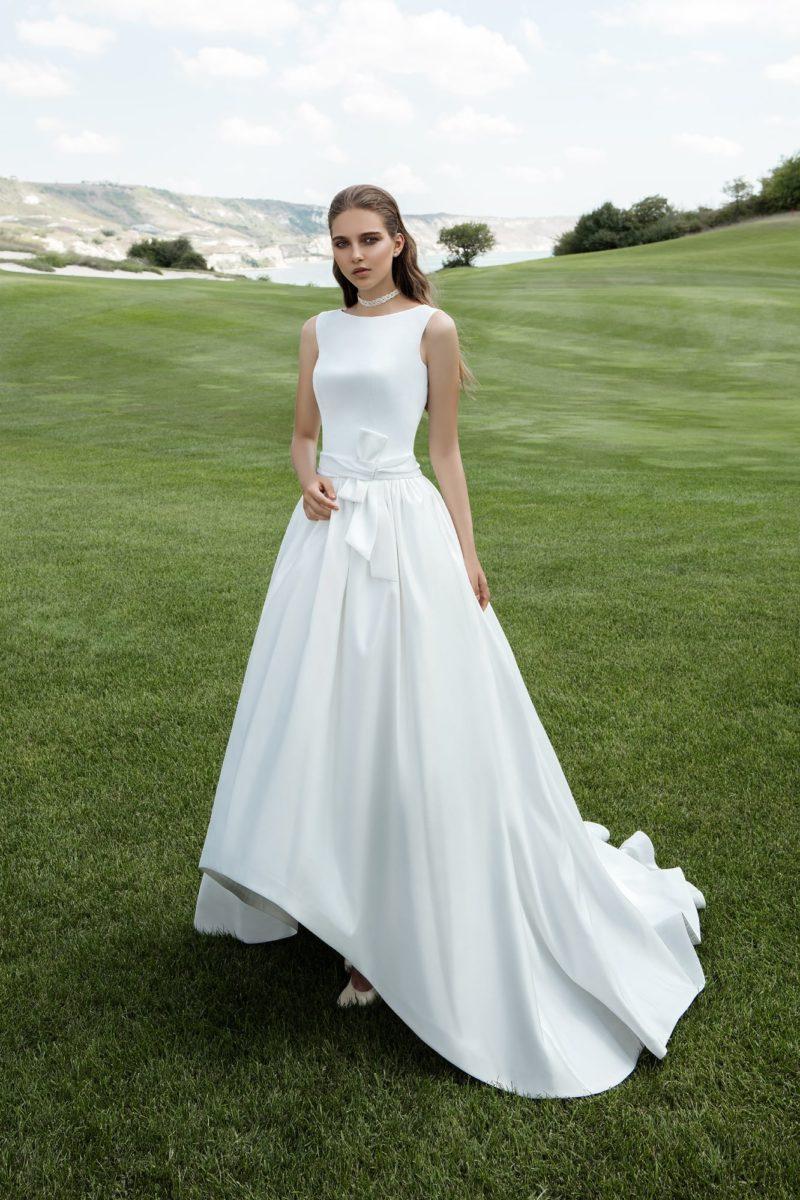 Атласное свадебное платье «принцесса» с вырезом лодочкой, поясом с бантом и укороченным спереди подолом.