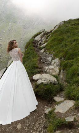 Лаконичное свадебное платье из атласа, с закрытым верхом и пышной юбкой со шлейфом.
