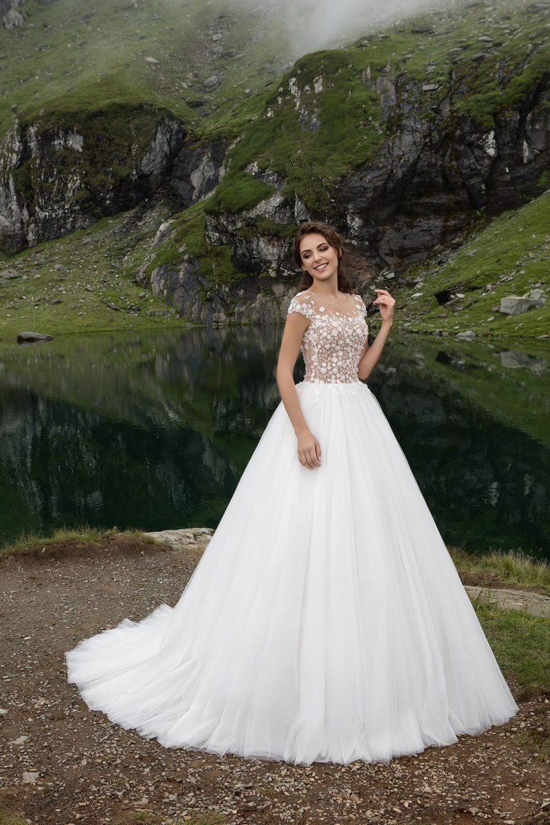 Свадебное платье с бежевым верхом с отделкой аппликациями и пышной юбкой.
