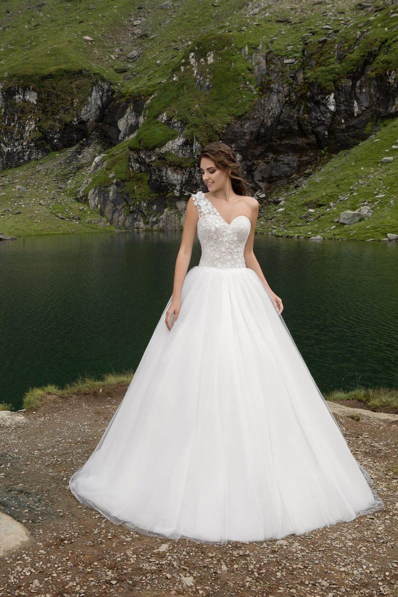 Нежное свадебное платье с асимметричным верхом и многослойной юбкой.