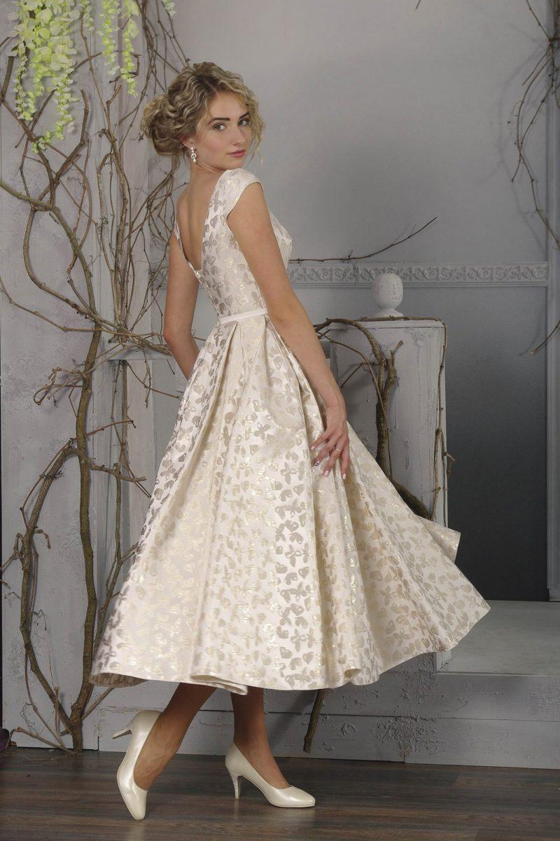 Оригинальное свадебное платье кремового оттенка, с юбкой чуть ниже колена и глянцевым узором.