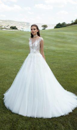 Пышное свадебное платье с полупрозрачным верхом и вертикальными складками по юбке.
