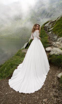 Впечатляющее свадебное платье с полупрозрачным верхом и пышной юбкой со шлейфом.