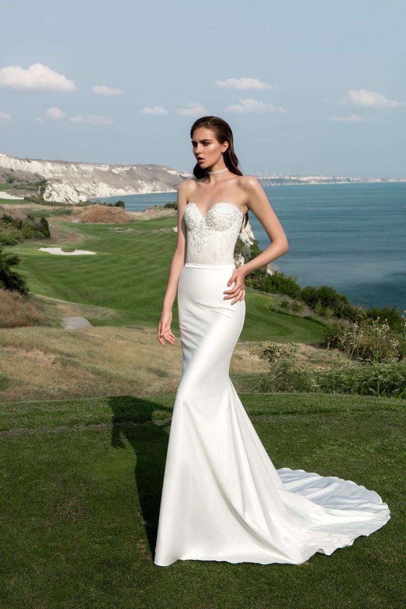 Открытое свадебное платье прямого кроя с вырезом в форме сердца и длинным шлейфом.