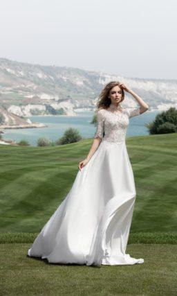 Закрытое свадебное платье прямого кроя с атласной юбкой и коротким кружевным рукавом.