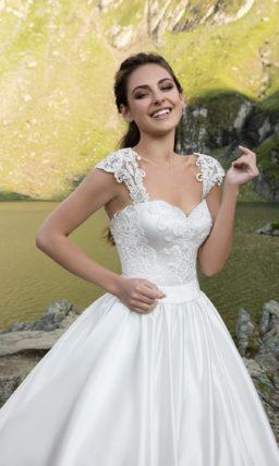 Пышное свадебное платье с роскошной юбкой из глянцевого атласа и широкими бретелями.