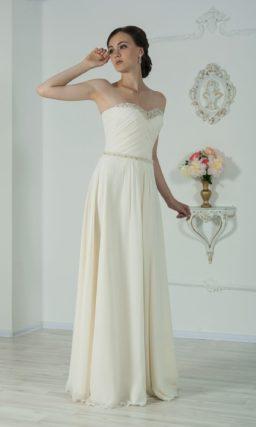 Прямое свадебное платье с лифом в форме сердечка и длинным полупрозрачным рукавом.