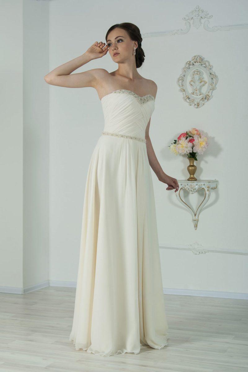 Стильное свадебное платье прямого кроя с открытым лифом, украшенным бисером по краю.