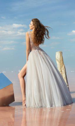 Белое вечернее платье с кружевным верхом и разрезом на юбке.