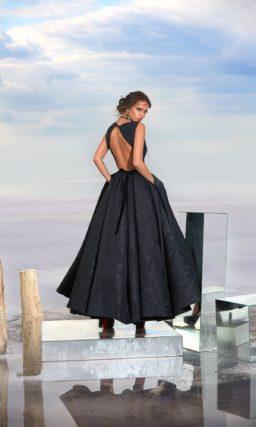 Закрытое вечернее платье из плотной черной фактурной ткани.