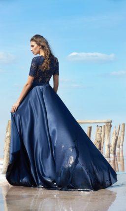 Закрытое вечернее платье синего цвета с прямой атласной юбкой.