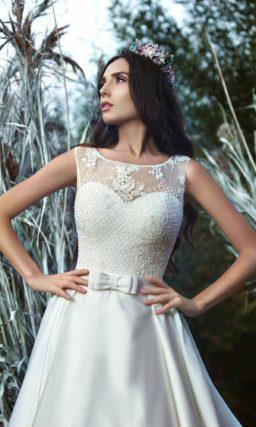 Изысканное свадебное платье из атласа с закрытым лифом и широким поясом с бантом.