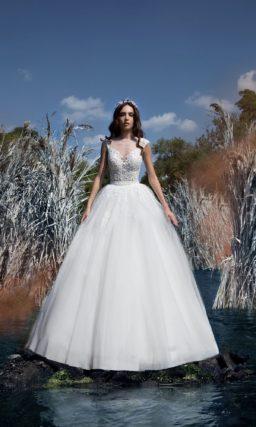 Пышное свадебное платье с фактурным лифом, оформленным прозрачной вставкой.