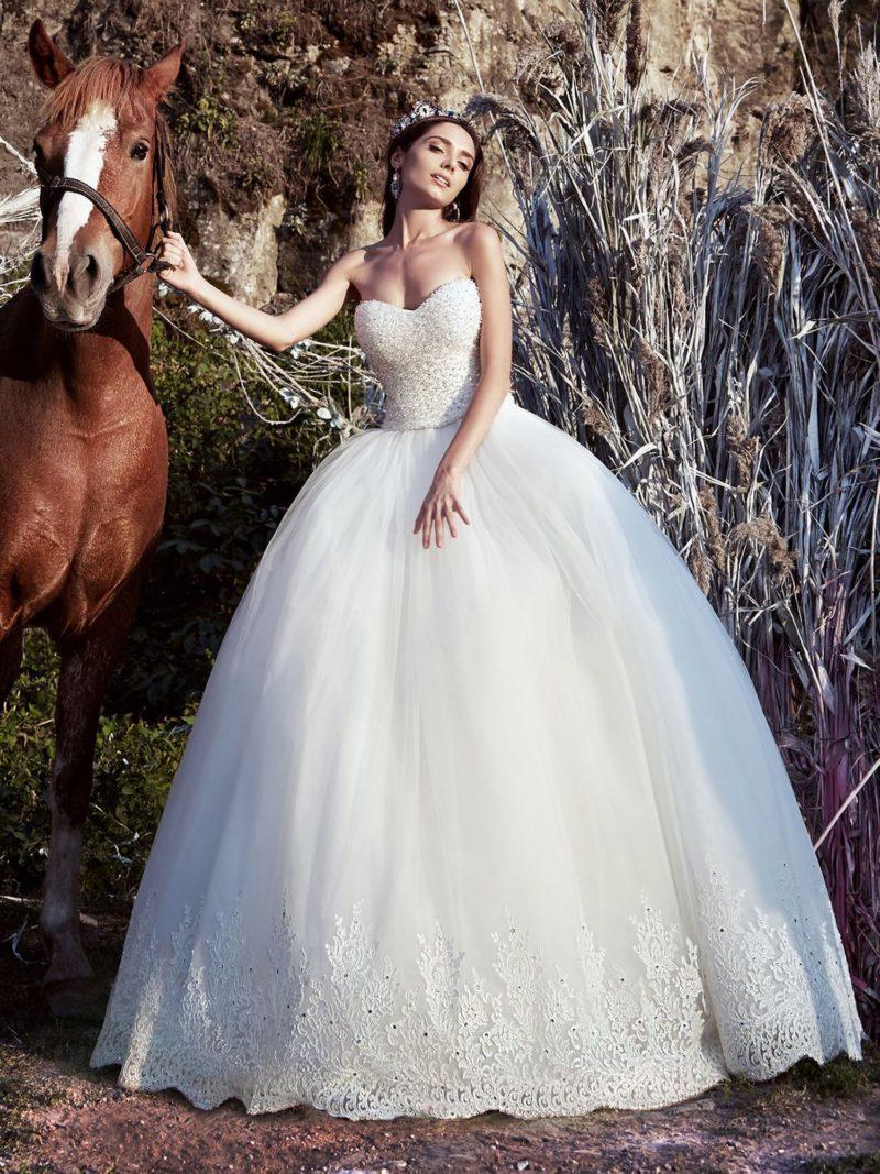 Потрясающее свадебное платье с открытым корсетом и воздушной юбкой с отделкой по низу подола.