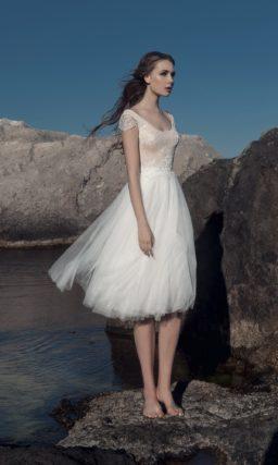 Нежное свадебное платье с округлым вырезом и многослойной юбкой до колена.
