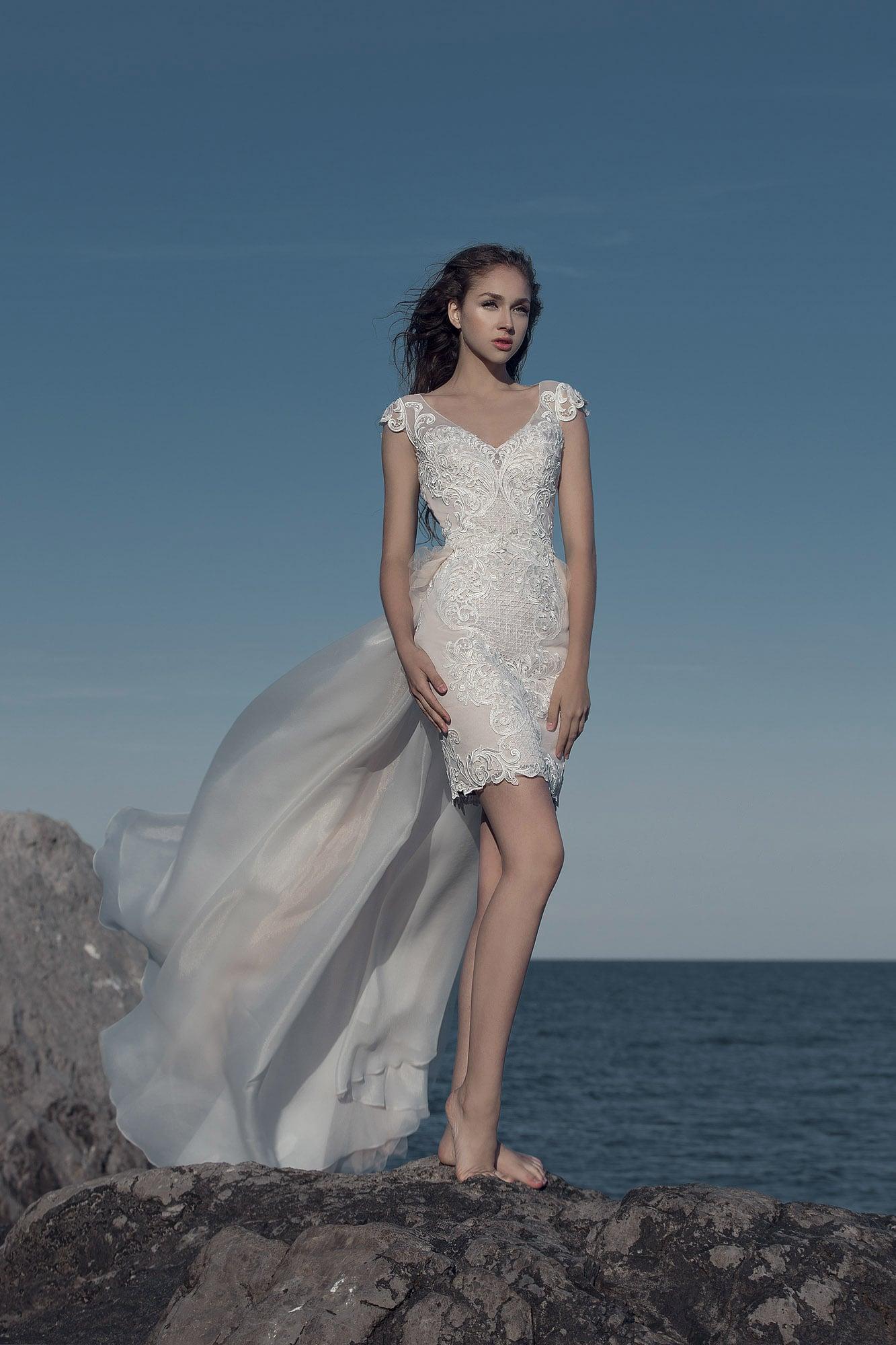 Короткое свадебное платье с бежевой подкладкой и коротким рукавом.