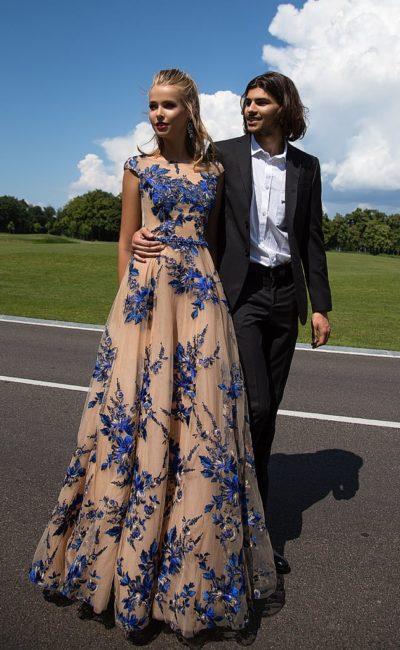 Пышное вечернее платье бежевого цвета, украшенное голубыми аппликациями по всей длине.