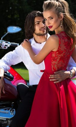 Лаконичное вечернее платье красного цвета с глубоким вырезом и длинным шлейфом.
