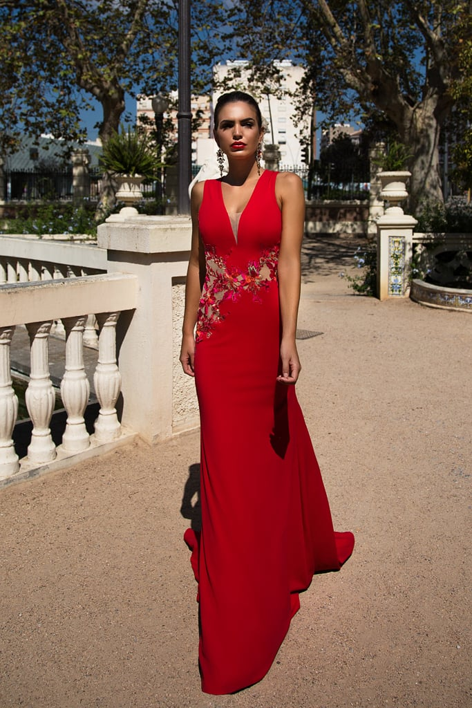 Впечатляющее вечернее платье алого цвета с глубоким V-образным вырезом декольте.