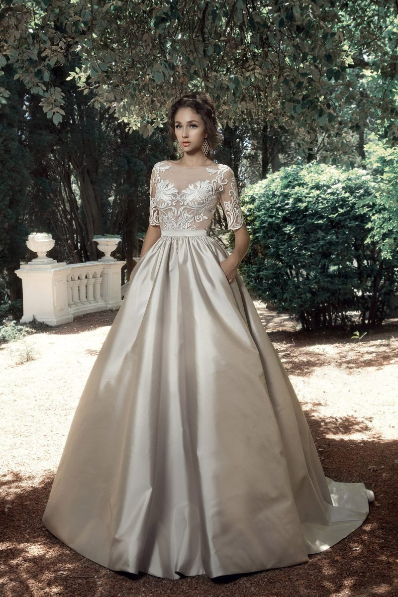 Бежевое свадебное платье пышного кроя с белым кружевом по верху.