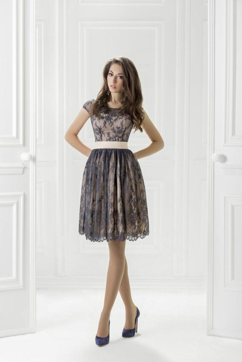 Бежевое вечернее платье до колена, украшенное синей кружевной тканью.