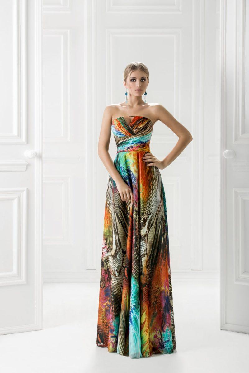Яркое вечернее платье с необычным принтом и широким поясом под лифом.