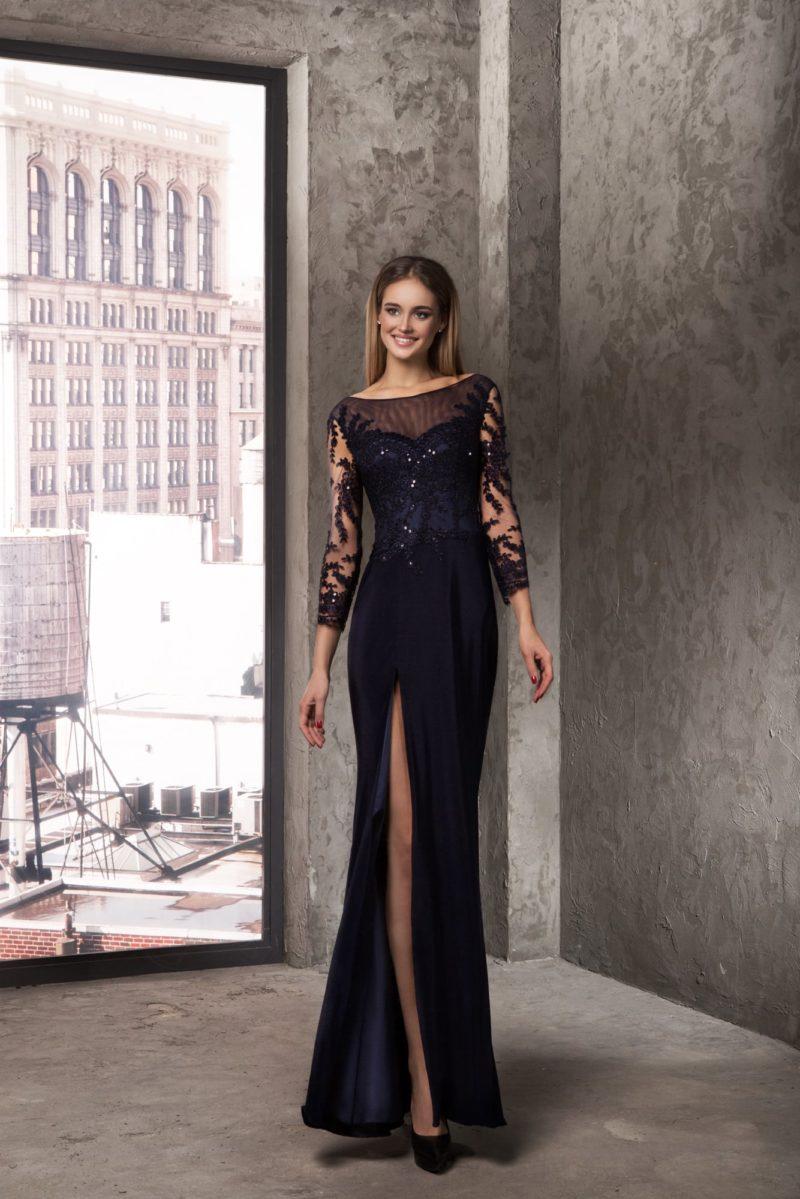 Прямое вечернее платье темно-синего цвета, оформленное тонкой тканью с кружевом.