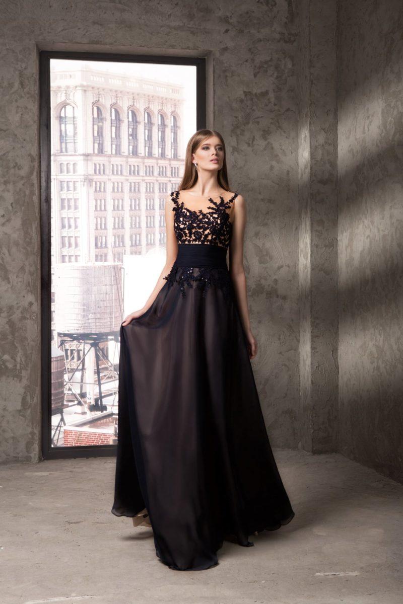 Вечернее платье на бежевой подкладке, украшенное черным кружевом и с поясом в тон.