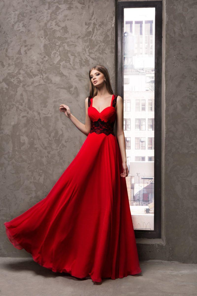 Прямое вечернее платье красного цвета с контрастной черной отделкой.