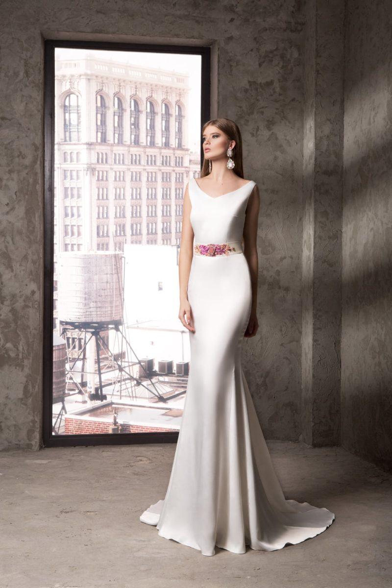 Атласное вечернее платье белого цвета с V-образным вырезом и цветной вышивкой на поясе.