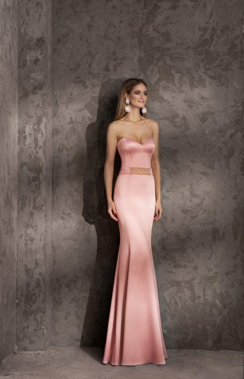 Изысканное вечернее платье из сияющей атласной ткани розового цвета, облегающее фигуру.