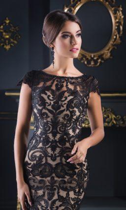 Черное вечернее платье из кружевной ткани с элегантной бежевой подкладкой.