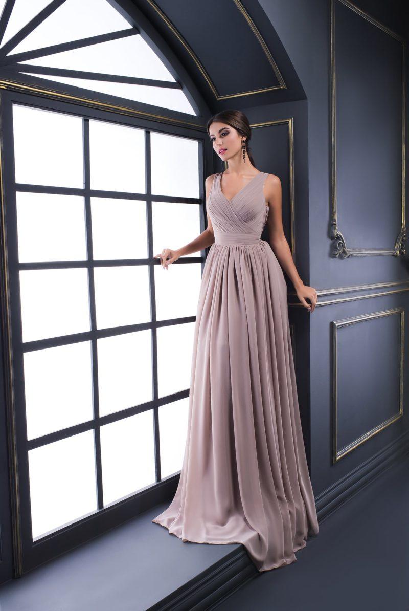 Песочно-бежевое вечернее платье с отделкой драпировками и V-образным вырезом.