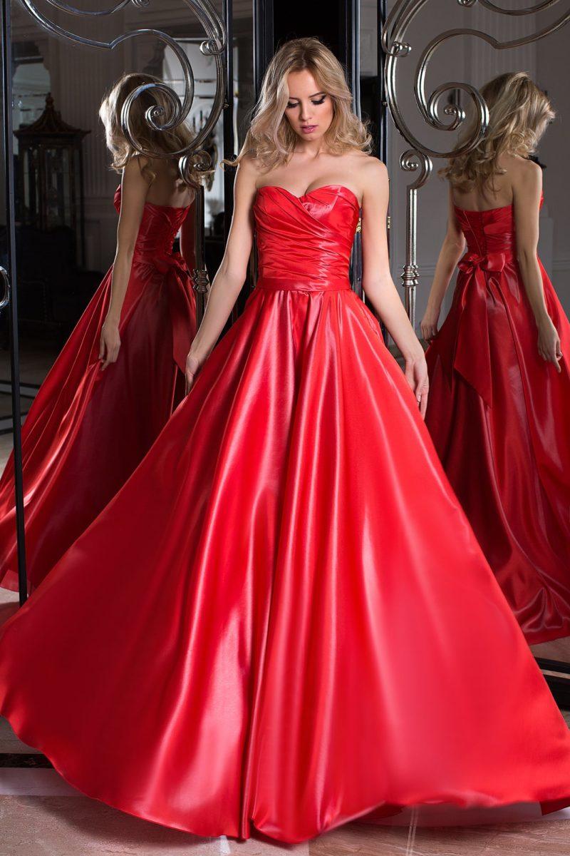Пышное вечернее платье красного цвета из фактурной ткани, украшенное на спине бантом.