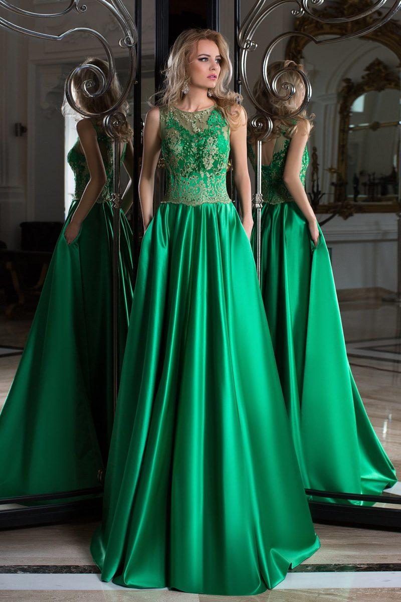 Прямое вечернее платье зеленого цвета, украшенное золотистым кружевом по корсету.