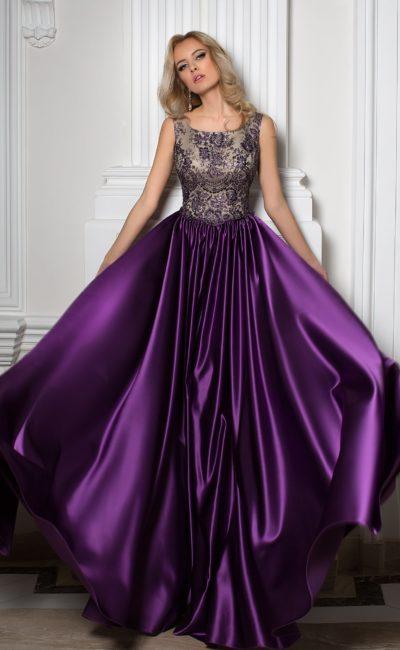 Фиолетовое вечернее платье с глянцевой юбкой и верхом из тонкой ткани на светлой подкладке.