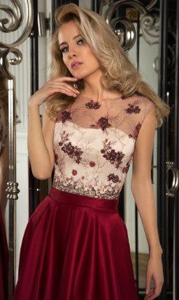 Вечернее платье с бордовой юбкой и светлым корсетом под тонкой тканью с вышивкой.