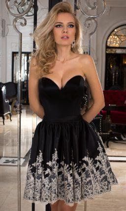 Короткое вечернее платье из глянцевой черной ткани, декорированное вышивкой по подолу.