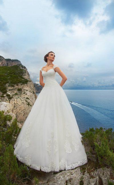 Пышное свадебное платье с широкими ажурными бретелями и аппликациями на юбке.