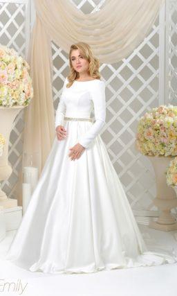 Атласное свадебное платье пышного кроя с длинным рукавом и роскошным шлейфом.