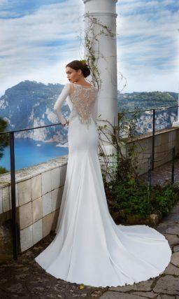 Прямое свадебное платье из плотного глянцевого атласа, с длинным рукавом и разрезом на юбке.