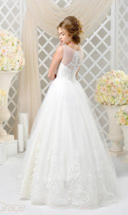Торжественное свадебное платье с изящным декором и прозрачной отделкой верха.