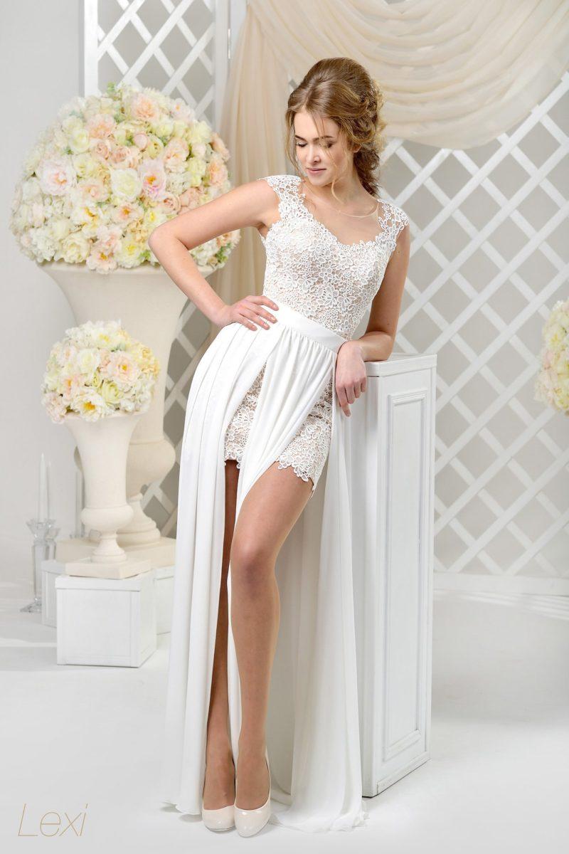 Свадебное платье с короткой кружевной юбкой, дополненной длинным верхом с разрезами.